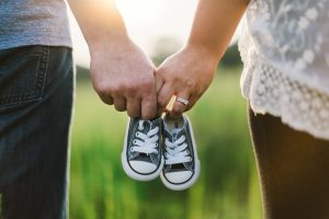Parents holding baby shoes in between their hands
