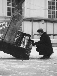 Broken piano lying on its side