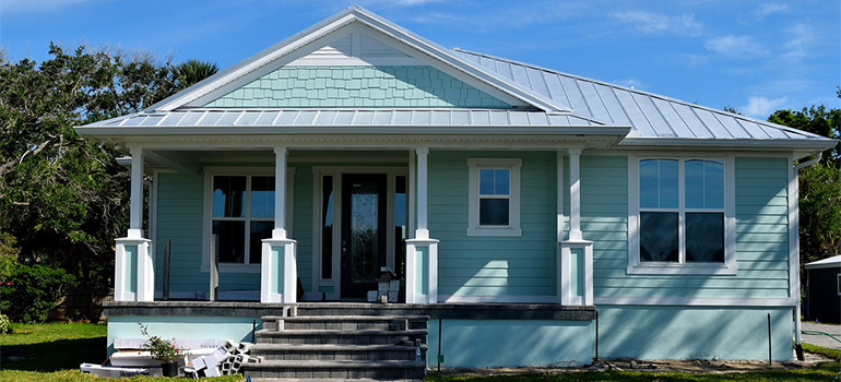 A blue house with a porch that movers Northwood NH can help you move into.