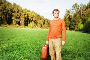 A man in nature with a suitcase in his hand