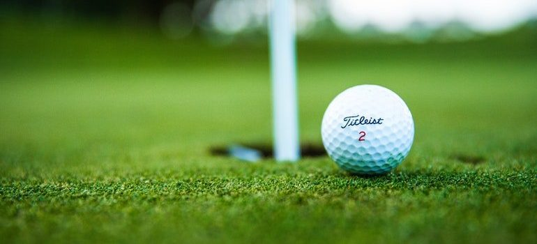 Close up of a golf ball at a hole.