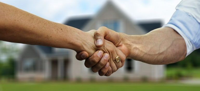 People shaking hands after buying a second home in Rye.