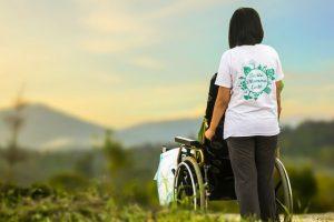 a woman with an elder in a wheelchair