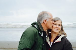 older man kissing his wife on the cheek by the ocean