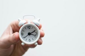 person holding a tiny white clock