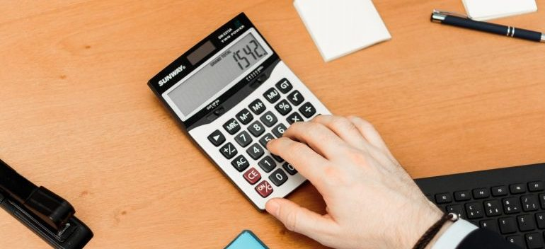 A person typing on a calculator