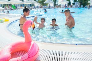 inflatable flamingo next to the pool and a family swimming