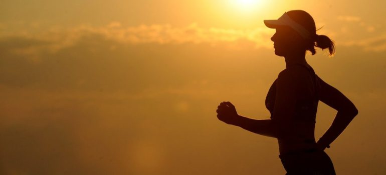 a silhouette of a woman jogging in the sunset as a way to stay in shape after moving internationally
