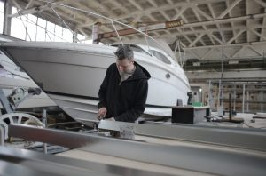 mechanic working on a boat indoors