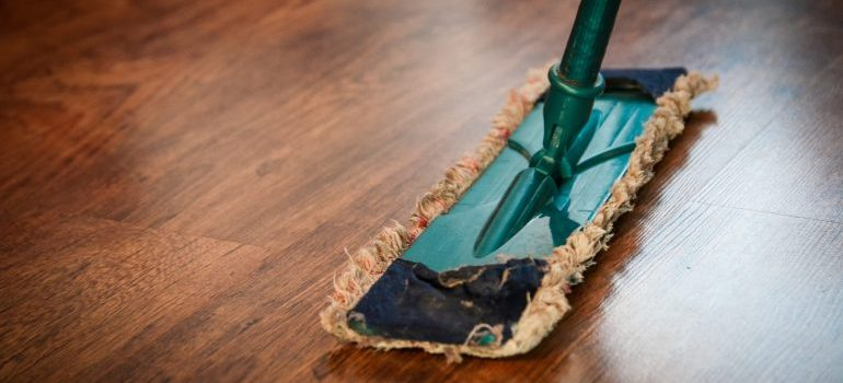 a mop cleaning a brown wooden floor