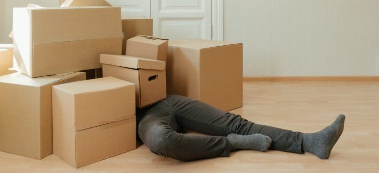 A person overwhelmed by moving boxes