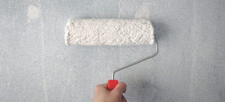 Person holding a paint roller