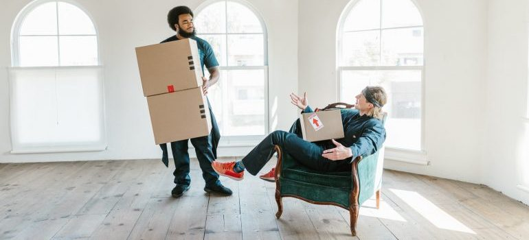 Two men carrying boxes.