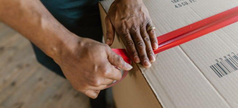 Man taping a box.