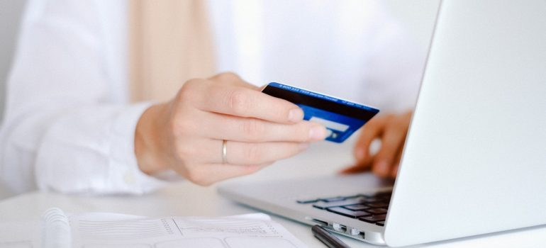 Woman holding credit card while typing on laptop