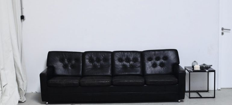 Black leather sofa next to a small table