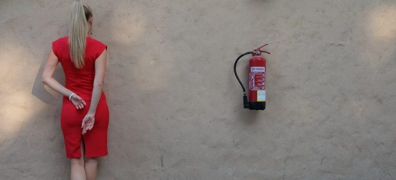 Woman in red facing a wall next to a fire extinguisher