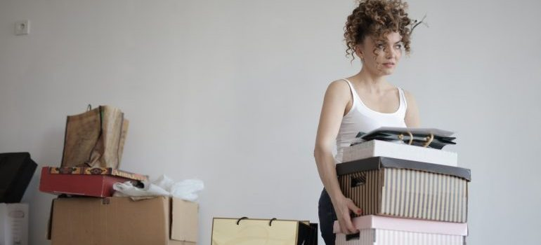 Woman carrying packed boxes